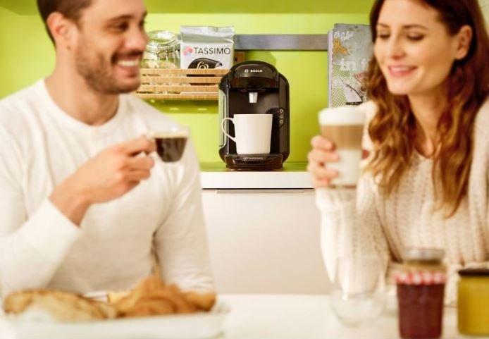 Muž a žena pijú kávu pripravenú v Bosch TAS 1402 Tassimo Vivy 2