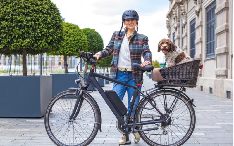 Mestský elektrobicykel, žena a pes v košíku