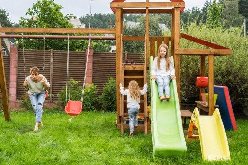 Mama s dvomi dcérami na detskom ihrisku na záhrade