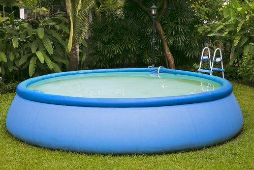 Modrý kruhový bazén so schodíkmi na záhrade