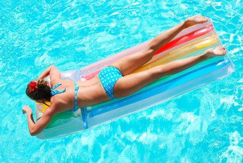 Žena sa opaľuje v bazéne na nafukovačke