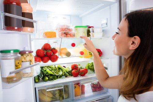 Mladá žena si vyberá jedlo z chladničky