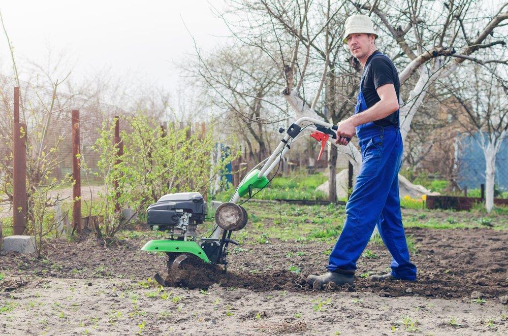 muž obrába pôdu kultivátorom