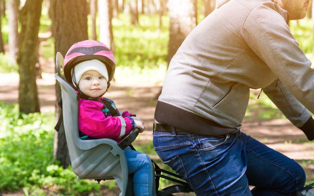 dieťa v detskej sedačke montovanej na zadný rám