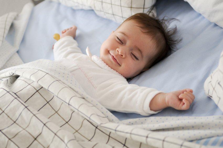 Usmievavé dieťa počas spánku na posteli
