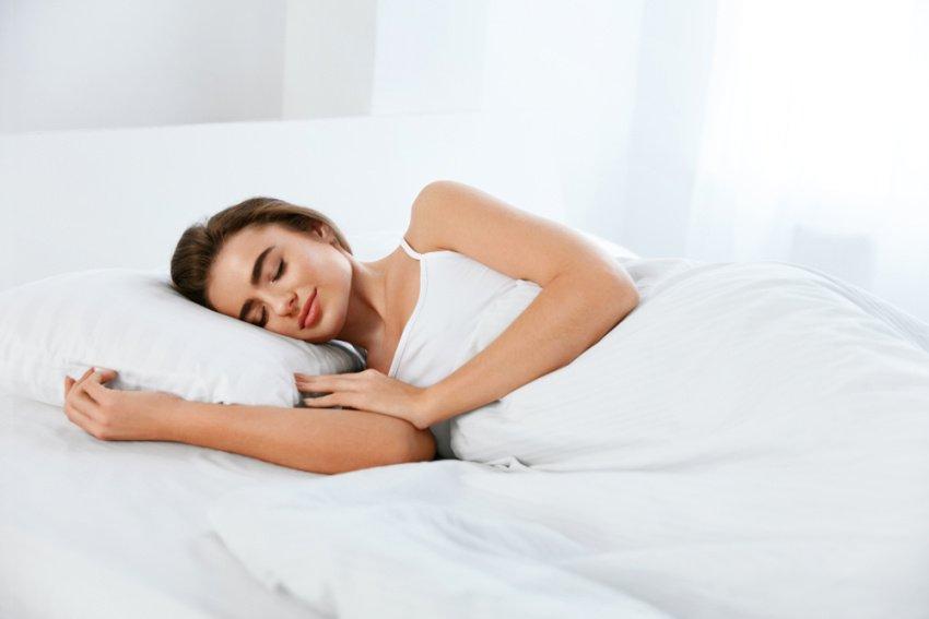 Žena spí na posteli s matracom a vankúšom