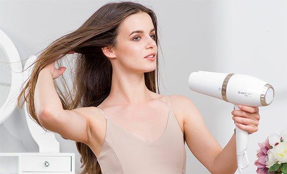 Žena si suší vlasy fénom Wellneo 2v1 AirPro