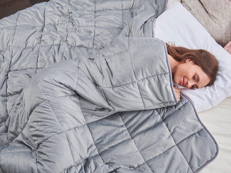 Žena spí pod antistresovou prikrývkou
