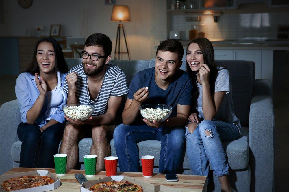 4 mladí ľudia s pukancami pred televízorom