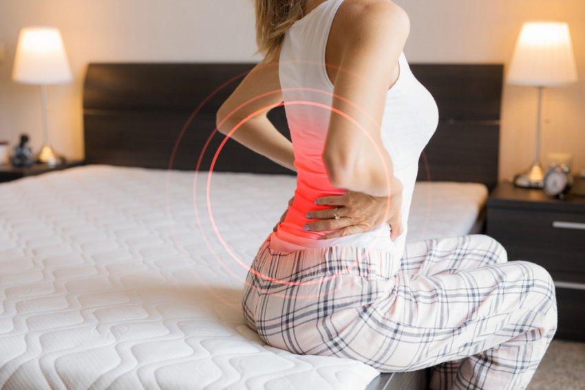 Žena na posteli má bolesti chrbtice