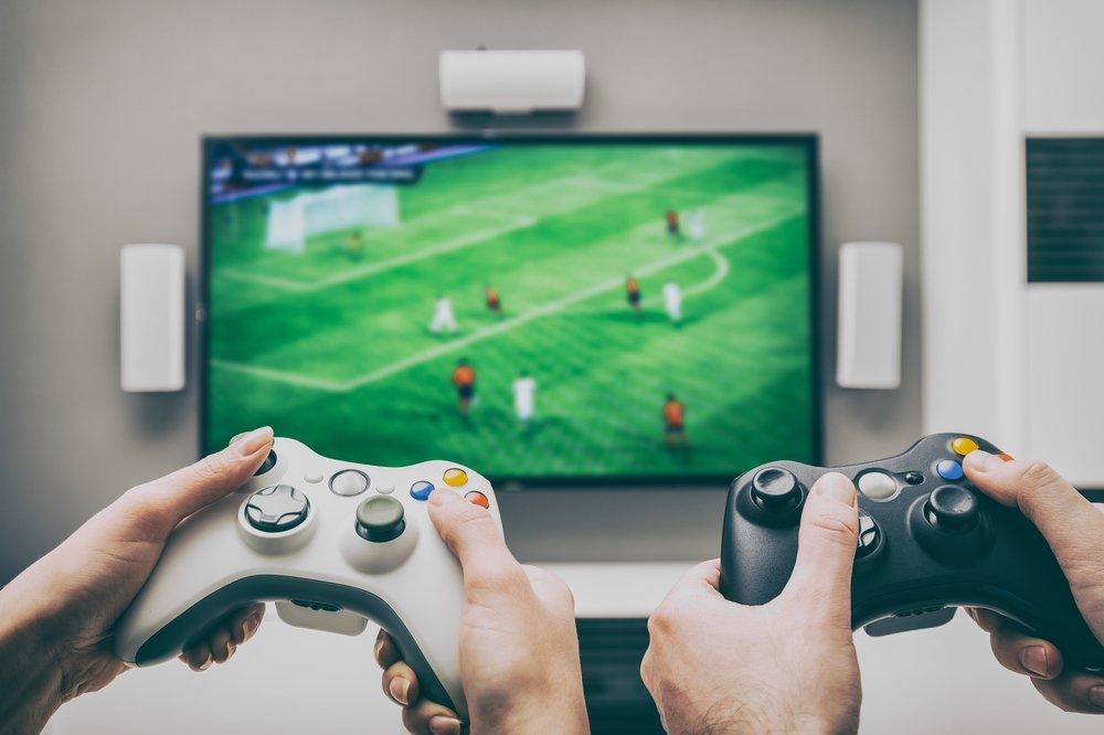 dvaja hrajú Fifu xbox ovládačmi pred TV