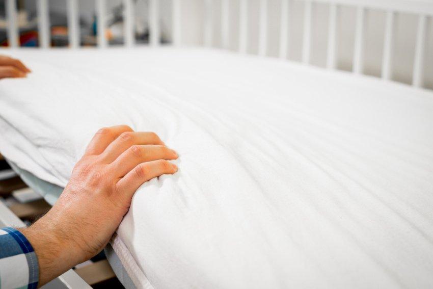 Muž ukladá matrac do detskej postieľky