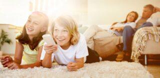 2 deti a rodičia pred televízorom