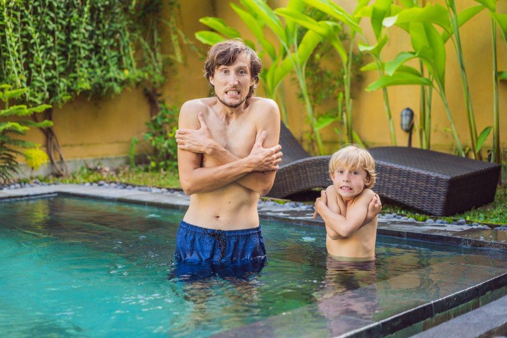 Otec a syn mrznú v studenej vode bazéna
