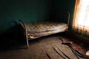 Starý, špinavý matrac na posteli v izbe za prirodzeného svetla