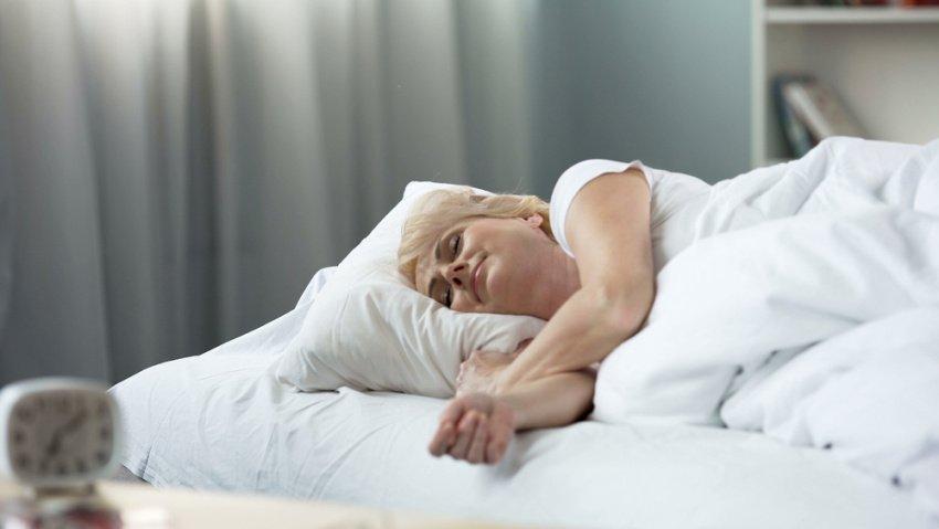 Žena pokojne spí na posteli