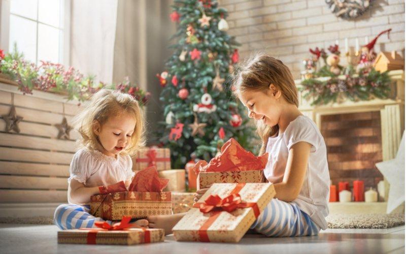 Dve dievčatká si rozbaľujú vianočné darčeky