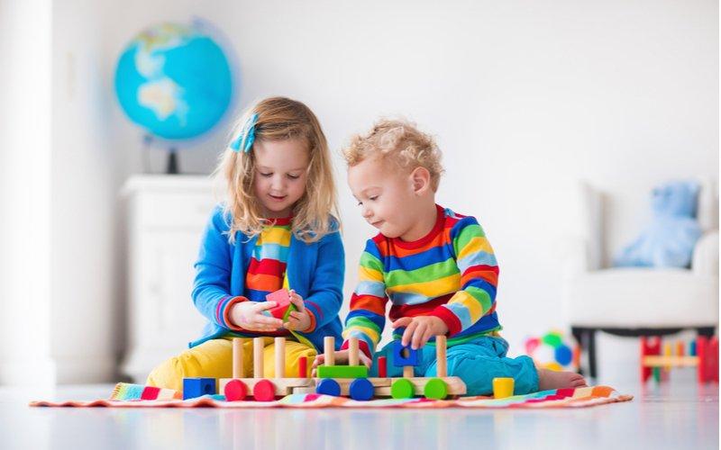 Dievčatko s chlapcom sa hrajú s dreveným vláčikom