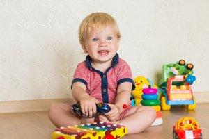 Malé dieťa sedí na zemi s hračkami