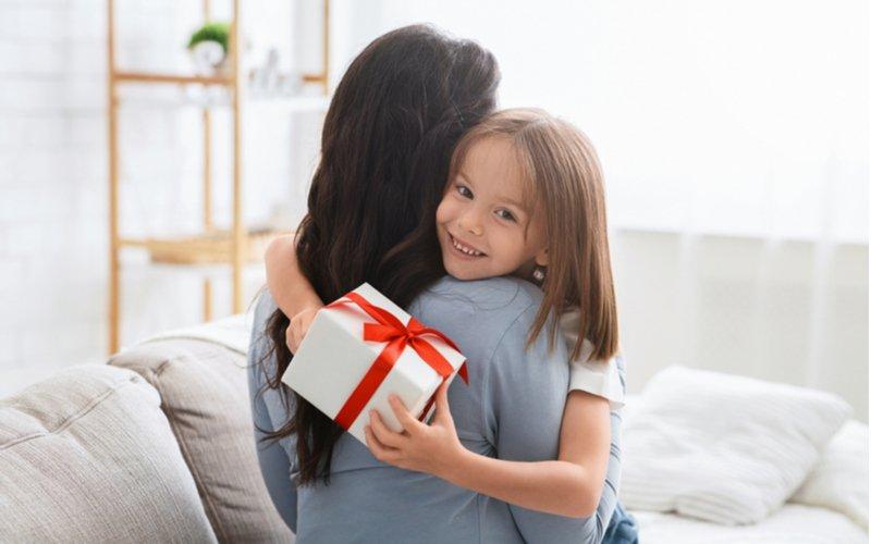 Dievčatko s darčekom v ruke objíma svoju mamu
