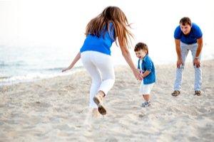 Žena s mužom a dieťaťom na pláži