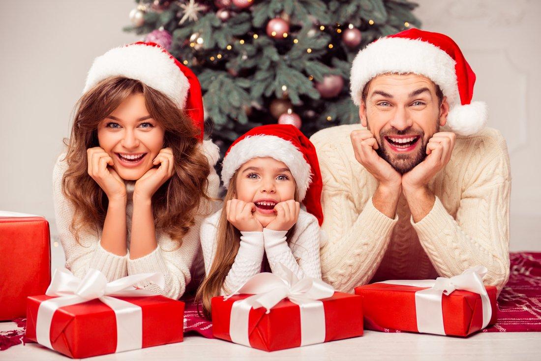 Rodinka vo vianočných čiapkach s darčekmi