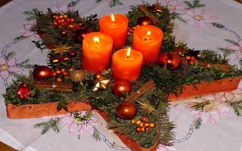 Štyri zapálené červené sviečky vo hviezdicovom adventnom venci