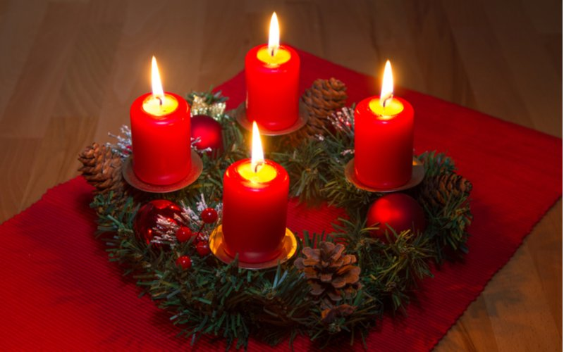Adventný veniec so zapálenými červenými sviečkami