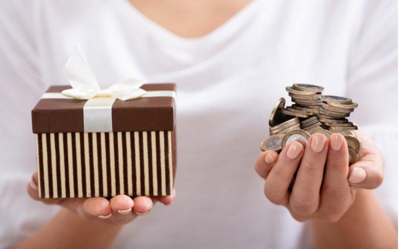 Žena drží v jednej ruke darček, v druhej mince
