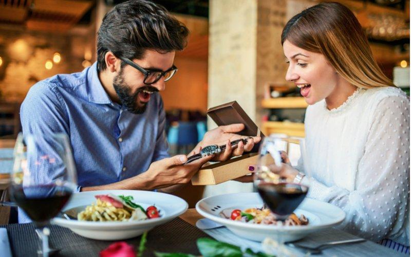Žena dáva darček priateľovi na večeri