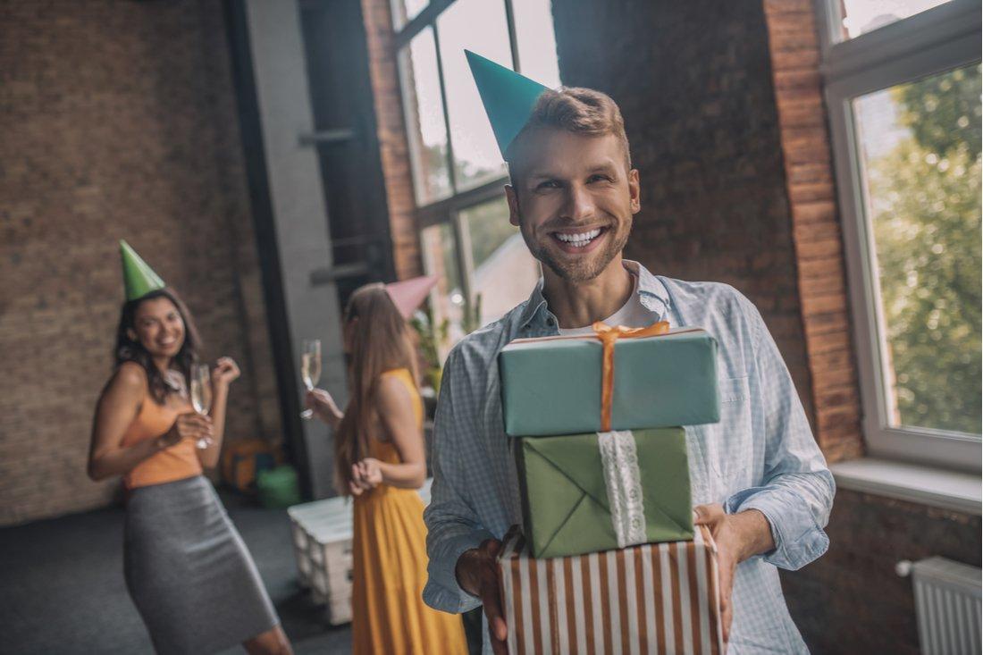 Usmiaty mladík s narodeninovými darčekmi