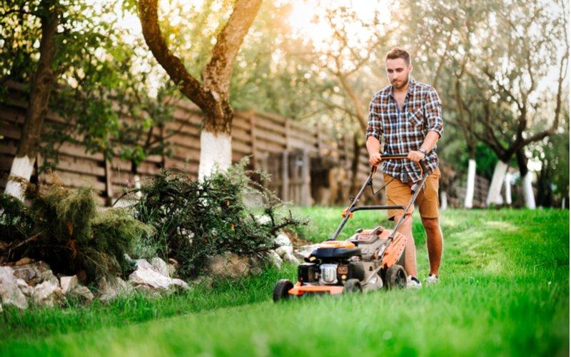 Muž kosí trávu kosačkou