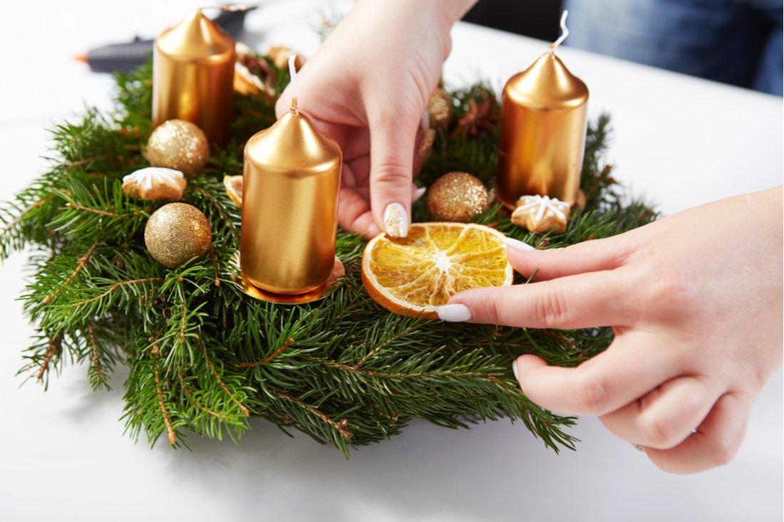 Žena lepí pomaranč na adventný veniec