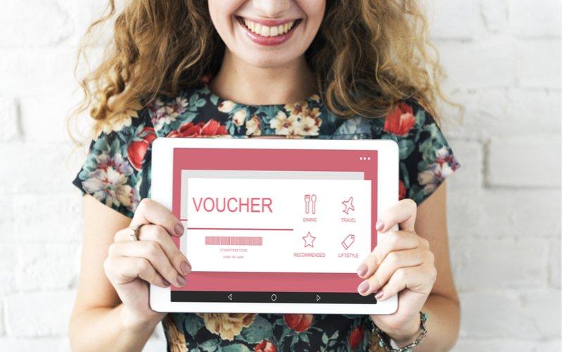 Usmiata žena drží voucher