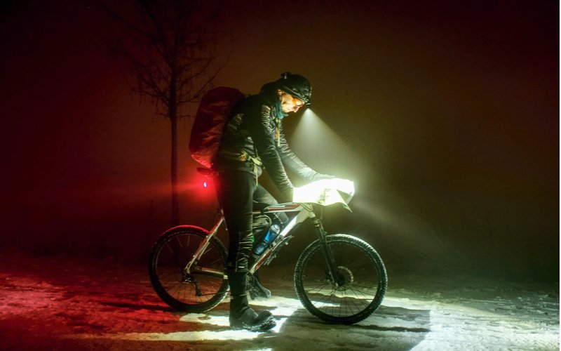 Cyklista si v tme svieti na mapu