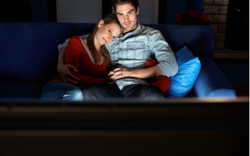 Muž so ženou pozerajú večer televízor