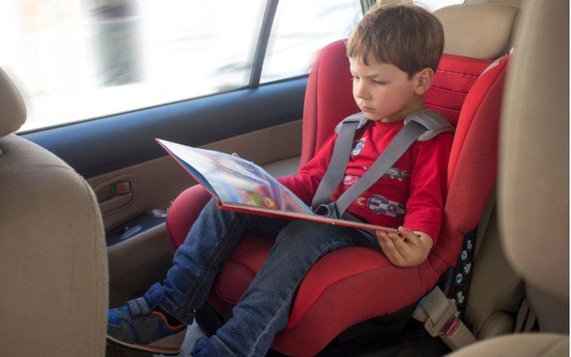 Autosedačky od 9 do 36 kg - bezpečnosť dieťaťa je najdôležitejšia, chlapec v autosedačke čítajúci knihu