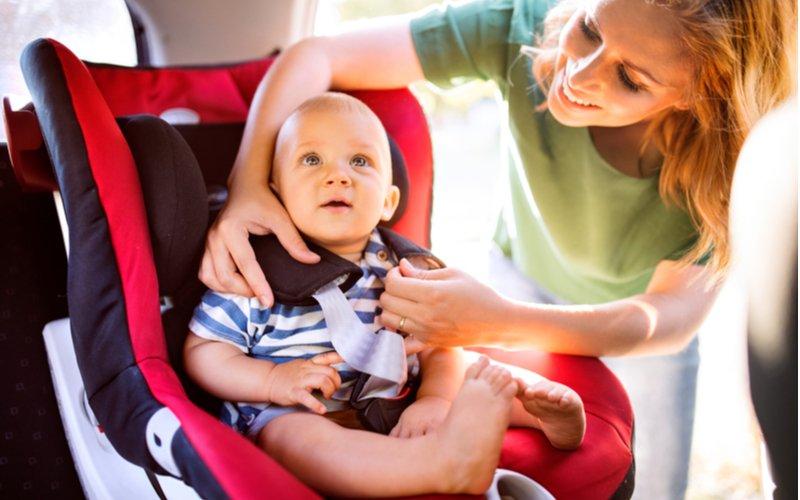 Žena zapína dieťa v autosedačke