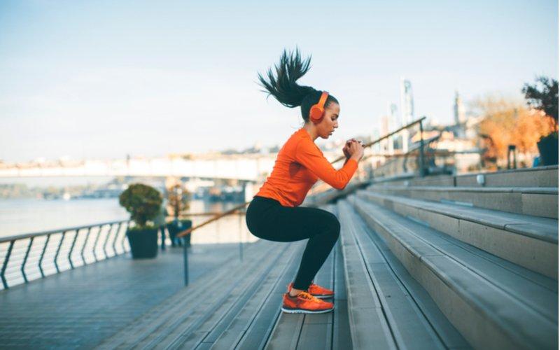 Žena v oranžovej mikine skáče po schodoch