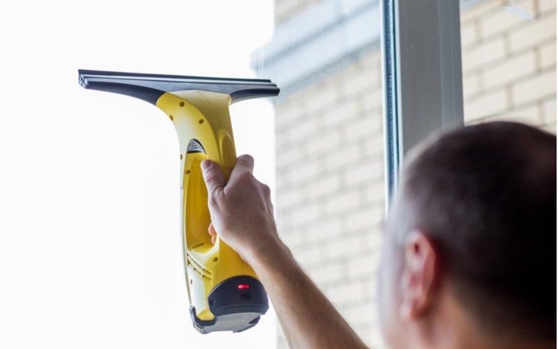 Muž umýva okno žltou akustierkou