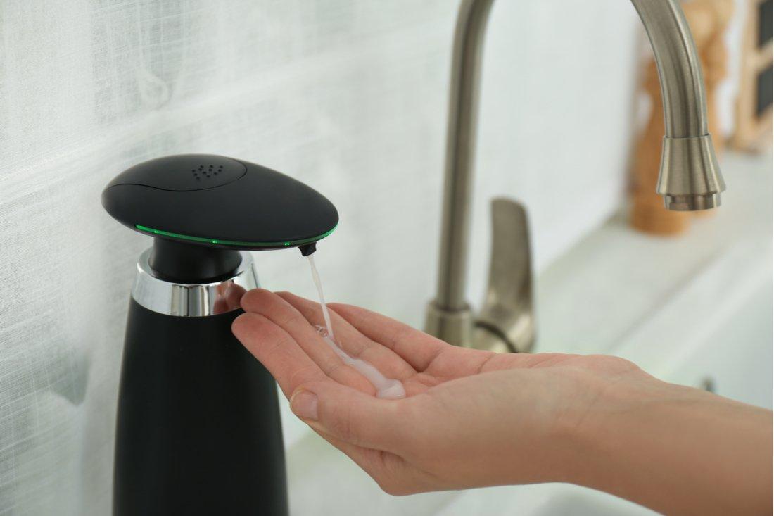 Čierny bezdotykový dávkovač mydla vydáva mydlo do ruky