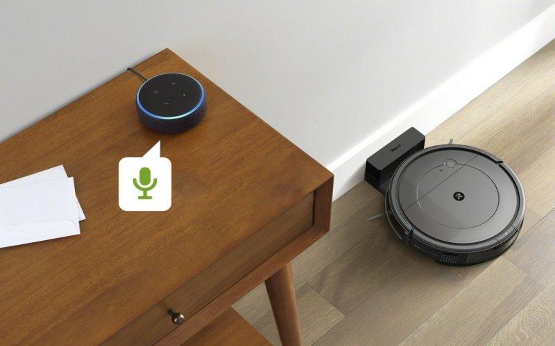 Hlasový asistent na stole a robotický vysávač na podlahe