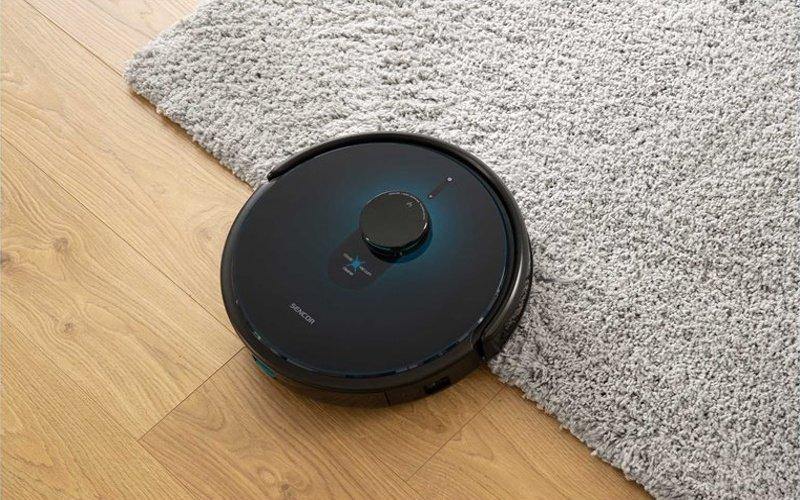 Robotický vysávač na podlahe a na koberci