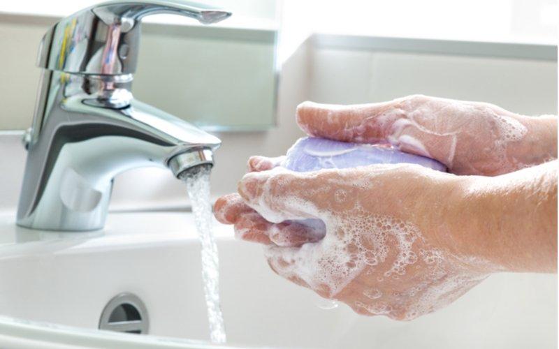 Umývanie rúk fialovým mydlom a prúd tečúcej vody
