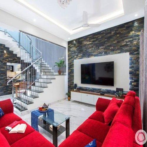 Obývačka c červenou pohovkou a kamenným obkladom na stene