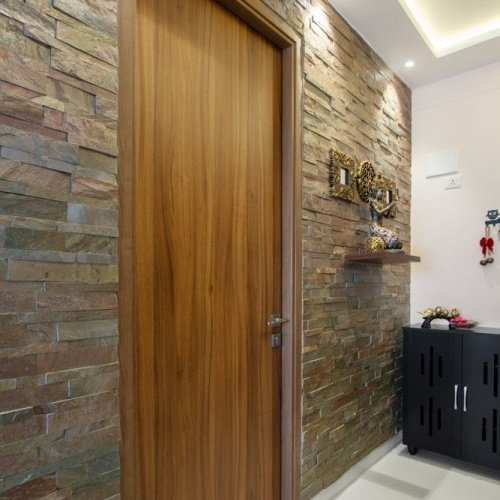 Hnedé dvere s kamenným obkladom na stene
