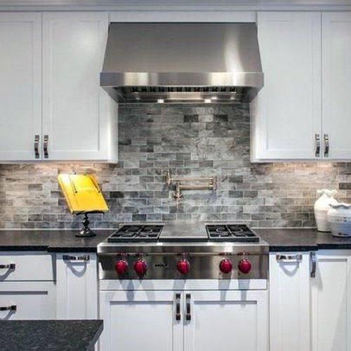 Biela kuchynská linka si sivým kamenným obkladom