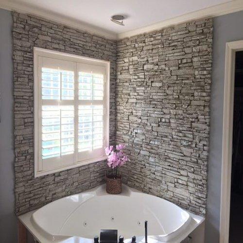 Kamenný obklad v kúpeľni s rohovou vaňou