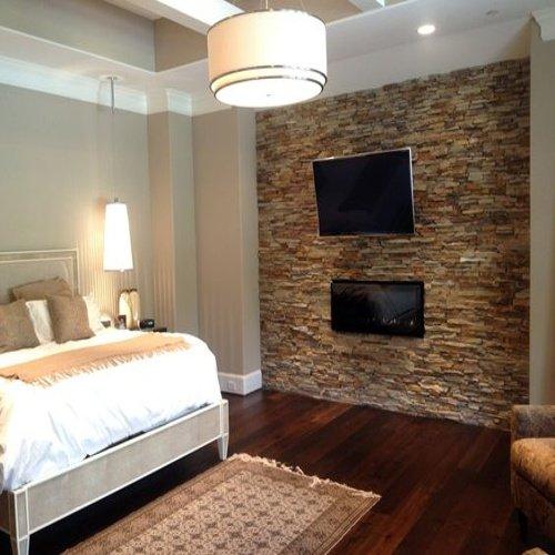 Spálňa s posteľou, televízorom a obkladom na stene
