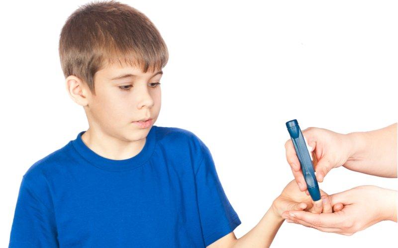 Chlapec v modrom tričku s glukomerom